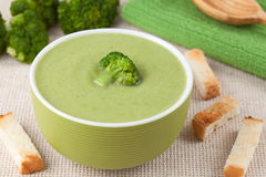 Green broccoli cream soup in a bowl with wooden. Spoon on textile background royalty free stock photo
