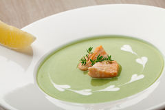 Green broccoli cream soup puree with filleted salmon  and  lemon. Green cabbage broccoli cream soup puree in white plate  served with  filleted salmon pieces Stock Photography