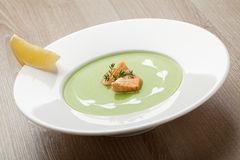 Green broccoli cream soup puree with filleted salmon  and  lemon. Green cabbage broccoli cream soup puree in white plate  served with  filleted salmon pieces Stock Photos