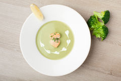 Green broccoli cream soup puree with filleted salmon  and  lemon. Green cabbage broccoli cream soup puree in white plate  served with  filleted salmon pieces Royalty Free Stock Photos