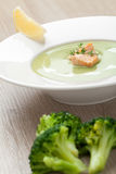 Green broccoli cream soup puree with filleted salmon  and  lemon. Green cabbage broccoli cream soup puree in white plate  served with  filleted salmon pieces Royalty Free Stock Photography