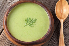 Green broccoli cream soup in a wooden bowl with Royalty Free Stock Photos
