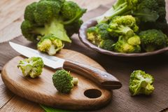 Green broccoli on a cutting board with a knife over wooden background. Bunch of fresh green broccoli on a cutting board with a knife over wooden background Royalty Free Stock Photos