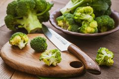 Green broccoli on a cutting board with a knife over wooden background. Bunch of fresh green broccoli on a cutting board with a knife over wooden background Royalty Free Stock Images