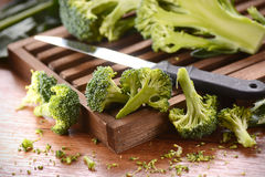 Green broccoli on cutting board. Green raw broccoli on wooden chopping board Stock Images