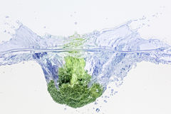 Green broccoli falling in water. On white with air bubbles and splashes Royalty Free Stock Photography