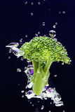 Green broccoli falling in water with air bubbles Royalty Free Stock Photography