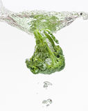 Green broccoli falling in water with air bubbles. Green broccoli falling in water on white with air bubbles royalty free stock images