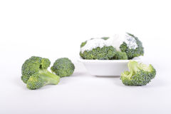 Green broccoli with white sauce on a white background Stock Photos