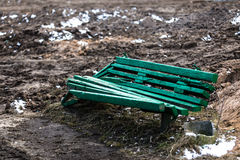 Green broken bench. With melting snow and dirt on background Stock Image