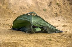 Broken tent at the beach. Green broken camping tent on the beach at the stormy weather Stock Images