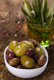 Green brown and black olives. Green and black olives in a white bowl on wooden background with foliage Stock Photos