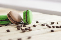 Green and brown french macarons with kiwi, coffee beans and mints decorations Stock Photography