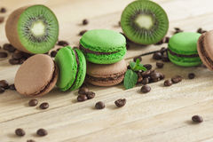Green and brown french macarons with kiwi, coffee beans and mints decorations Stock Images