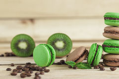 Green and brown french macarons with kiwi, coffee beans and mints decorations Royalty Free Stock Images