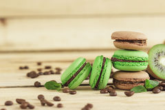 Green and brown french macarons with kiwi, coffee beans and mints decorations Stock Photo