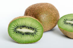 Green and Brown Kiwis on White. One Whole Kiwi and One Halved to See the Inside stock photos