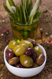 Green and brown olives. In a white bowl on wooden background with foliage Stock Photos