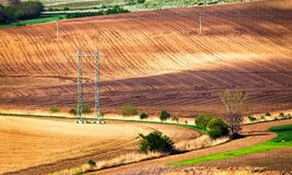 Green and brown spring ploughland. Rolling arable fields. In Czech Moravia Stock Image