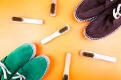 Green and brown suede espadrille shoes with brushes on yellow paper background. Stock Images