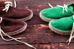 Green and brown suede espadrille shoes on wooden background. Stock Image