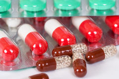 Green, brown and white-and-red antibiotic capsules Royalty Free Stock Images