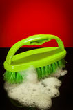 Green brush with soap suds Royalty Free Stock Images