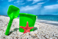 Green bucket and spade by the sea in hdr Royalty Free Stock Photography