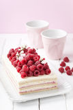 Green buckwheat cake with cream and fresh raspberries. Selective focus Stock Images