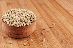 Green buckwheat in wooden bowl on brown bamboo board, close up. Healthy food background Stock Image