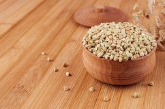 Green buckwheat in wooden bowl on brown bamboo board, close up. Rustic style, healthy dietary groats  background Royalty Free Stock Image