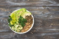 Green Buddha Bowl with lentils, quinoa, avocado, cucumber, fresh lettuce, herbs and seeds. Delicious healthy balanced eating. On a wooden background, top view Royalty Free Stock Photography