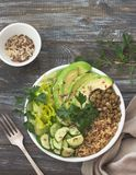 Green Buddha Bowl with lentils, quinoa, avocado, cucumber, fresh lettuce, herbs and seeds. Delicious healthy balanced eating. On a wooden background, top view Royalty Free Stock Images