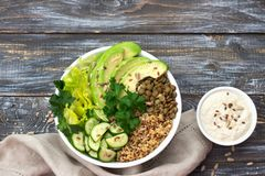 Green Buddha Bowl with lentils, quinoa, avocado, cucumber, fresh lettuce, herbs and seeds. With tahini sauce. Delicious healthy balanced eating. On a wooden Royalty Free Stock Photo