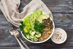 Green Buddha Bowl with lentils, quinoa, avocado, cucumber, fresh lettuce, herbs and seeds. With tahini sauce. Delicious healthy balanced eating. On a wooden Royalty Free Stock Image