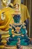 Green buddha among other buddhas. Beautiful green buddha among other gold buddhas in temple in bangkok royalty free stock image