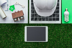 Green building and alternative energies. Eco house and sustainable building concept: work tools, solar panel and drafts on the grass, digital tablet at center royalty free stock photo