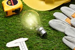 Green building and energy saving concept: house projecj and work. Tools on the grass stock image