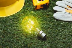 Green building and energy saving concept: house projecj and work. Tools on the grass stock photography