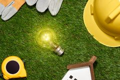 Green building and energy saving concept: house projecj and work. Tools on the grass royalty free stock photography