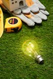 Green building and energy saving concept: house projecj and work tools on the grass.  royalty free stock photography