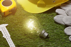 Green building and energy saving concept: house projecj and work. Tools on the grass royalty free stock image