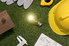 Green building and energy saving concept: house projecj and work. Tools on the grass royalty free stock images