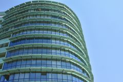 Green building with offices and glass windows. Modern green building with offices and glass windows Royalty Free Stock Images