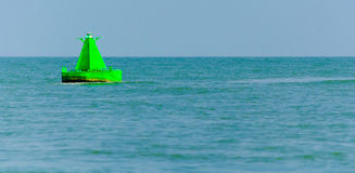 Green buoy. A neon green buoy in the midle of the sea Royalty Free Stock Image