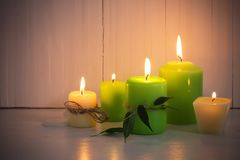 Green burning candles on white background. Green burning candles on a white background stock image