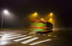 Green bus in dark foggy autumn evening Stock Photo