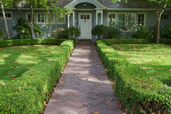 Green bush lined home entrance Stock Images