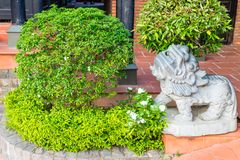 Green bush with lion statue of stone. Green bush with ancient lion statue of stone royalty free stock photo