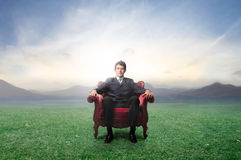 Green business. Businessman sitting on an armchair on a green meadow Stock Images